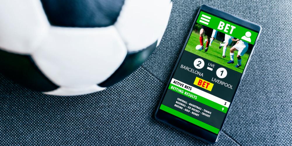 Zakłady bukmacherskie związane z piłką nożną z pomocą aplikacji mobilnej.